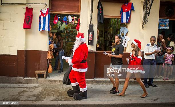 People wearing costumes of Santa give out leaflets promoting a restaurant in the streets of Havana on December 23 2014 Last week President Barack...