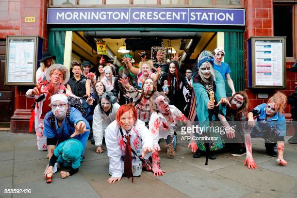 People wearing costumes pose for a photograph as they gather outside a London Underground station before participating in a Zombie Walk on World...