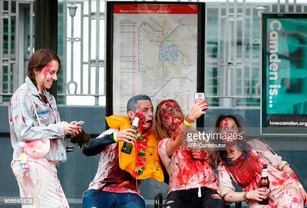 People wearing costumes pose for a selfie photograph as they gather at a bus stop before participating in a Zombie Walk on World Zombie Day in London...