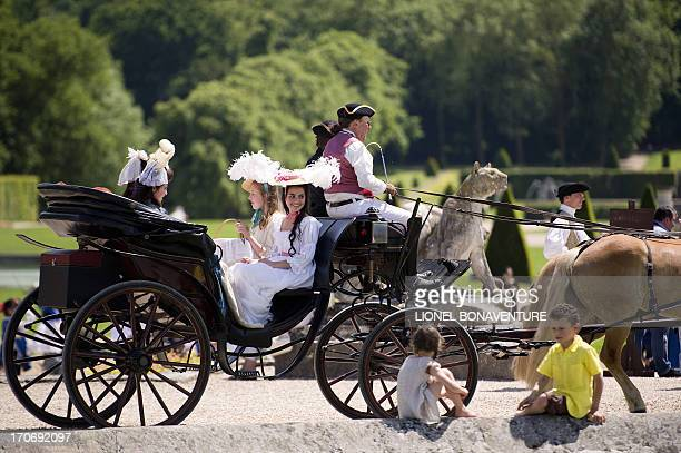 """People wearing costumes ride a carriage in the Vaux-Le-Vicomte castle during the """"Journee Grand Siecle"""" on June 16, 2013 in Maincy. This event aims..."""
