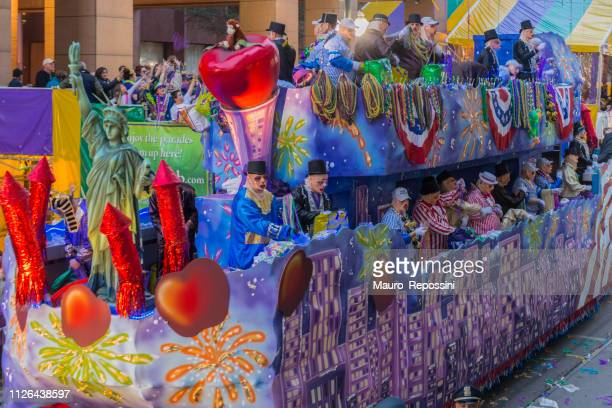 people wearing costumes standing on a float parade in the street during the mardi gras celebration at new orleans carnival, louisiana, usa. - mardi gras parade stock photos and pictures