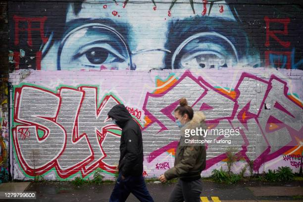 People wearing Covid-19 protective face masks walk past the remnants of a John Lennon mural on October 12, 2020 in Liverpool, England. Under a new...