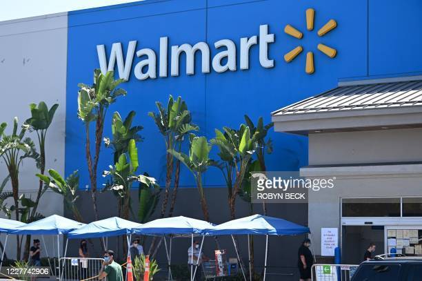 People wearing face coverings wait in line to shop at Walmart, July 22, 2020 in Burbank, California. - The country's most populous state reported a...