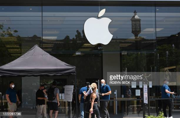 People wearing face coverings wait to enter the Apple Store at the Americana at Brand shopping, dining and entertainment mall complex in Glendale,...