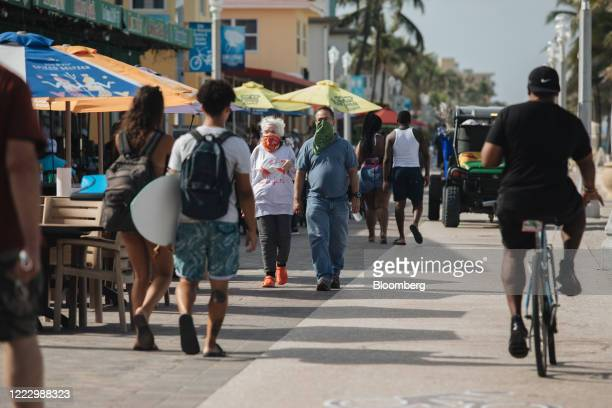 People wearing face coverings walk on a boardwalk in Hollywood, Florida, U.S., on Thursday, June 25, 2020. On Thursday, Florida reported more than...