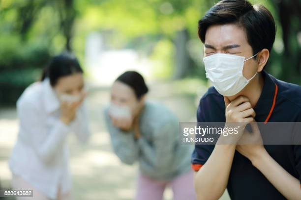 people wearing face mask and coughing - flu mask stock photos and pictures