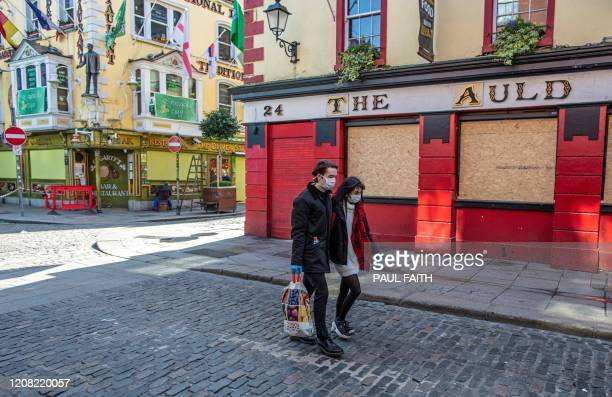 People wearing face mask as a precautionary measure against Covid19 carry a shopping bag as the pass a boardedup and temporarily closed pub in Dublin...
