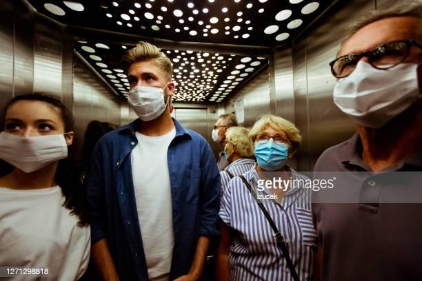 mensen die gezichtsmasker in lift dragen - izusek stockfoto's en -beelden