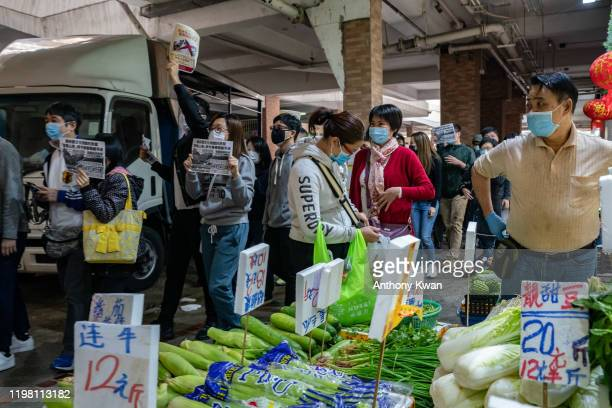 People wearing face mask purchase produce at a wet market as residents of Mei Foo protest against government plans to convert the Jao Tsung-I Academy...