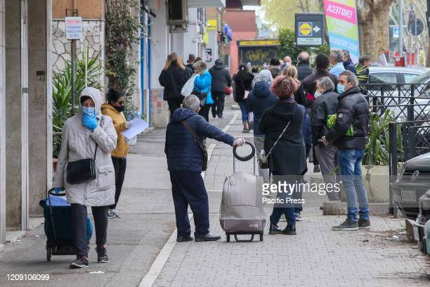 People wearing face mask walk on the street in Rome's Magliana district as the spread of coronavirus disease continues in Italy Italian government...