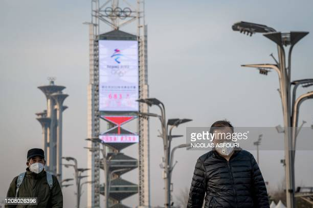 People wearing face masks, amid concerns of the COVID-19 coronavirus, walk at the Olympic park outside the national 'Birds Nest' stadium , the main...