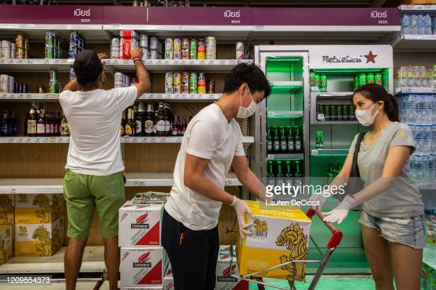 People wearing face masks and gloves purchase cases of beer at a Big C supermarket the night before a citywide alcohol ban on April 9, 2020 in...