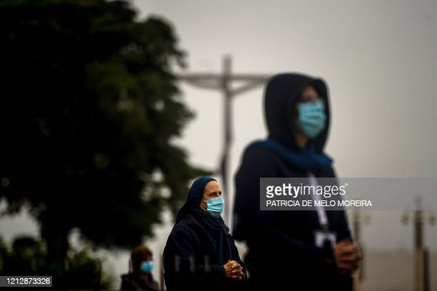 People wearing face masks and keeping their social distance, attend the 103rd anniversary of the apparitions of Our Lady of Fatima at the Fatima...