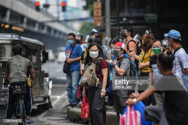 People wearing face masks and shields to protect themselves against the Covid-19 coronavirus wait for their transport on a street in Manila on...