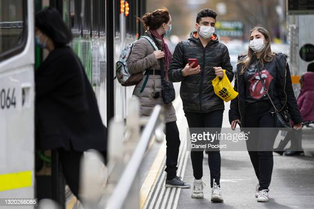 People wearing face masks are seen boarding and disembarking a tram on May 27, 2021 in Melbourne, Australia. There are now 34 cases linked to a...