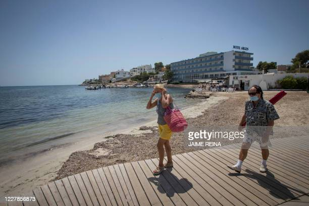 People wearing face masks arrive at Talamanca beach in Ibiza, on July 31, 2020. - With Spanish health authorities struggling with a rising number of...