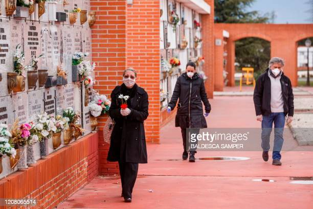 TOPSHOT People wearing face masks arrive at the South Municipal cemetery in Madrid on March 23 to attend the burial of a man who died of the new...