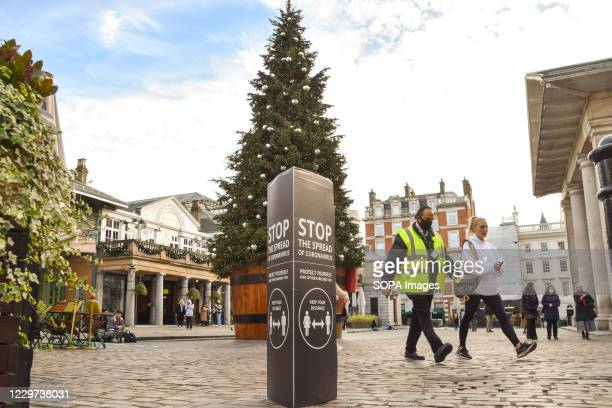 People wearing face masks as a precaution walk past a Stop The Spread Of Coronavirus sign next to the Christmas tree in Covent Garden. England is set...
