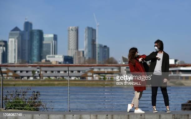 TOPSHOT People wearing face masks as a precautionary measure against covid19 'elbow bump' as they stand in Greenwich in south London backdropped by...