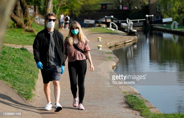 People wearing face masks as a precautionary measure against COVID19 walk on the towpath by Regent's Canal in east London on April 11 as life in...
