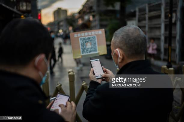 """People wearing face masks as a preventive measure against the Covid-19 scan a QR code with their smartphones to check their """"Health Kit"""" to enter an..."""