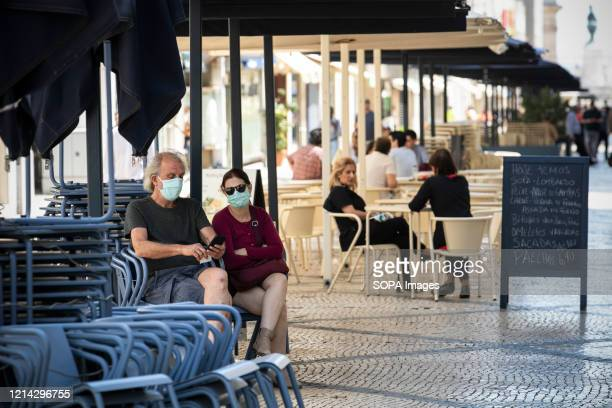 People wearing face masks as a preventive measure against the spread of coronavirus relax at a recently reopened restaurant terrace in downtown...