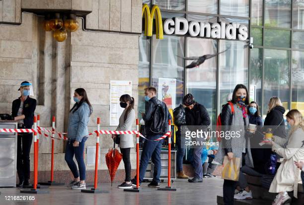 People wearing face masks as a preventive measure against the spread of coronavirus are seen waiting outside McDonald's restaurant for their orders...