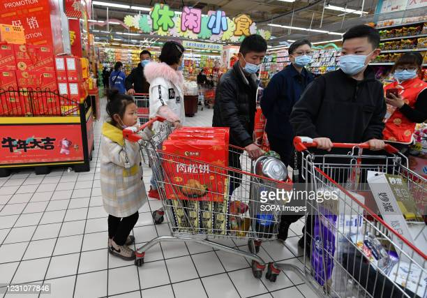 People wearing face masks as a preventive measure against the spread of Covid19 shop for the Chinese New Year in rt-mart supermarket of Fuyang....
