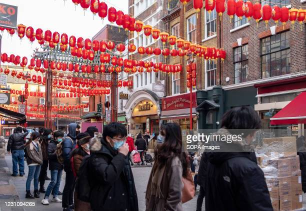 People wearing face masks as a preventive measure against the spread of covid-19 queue in front Chinese shop in China Town, London. Chinese New Year...