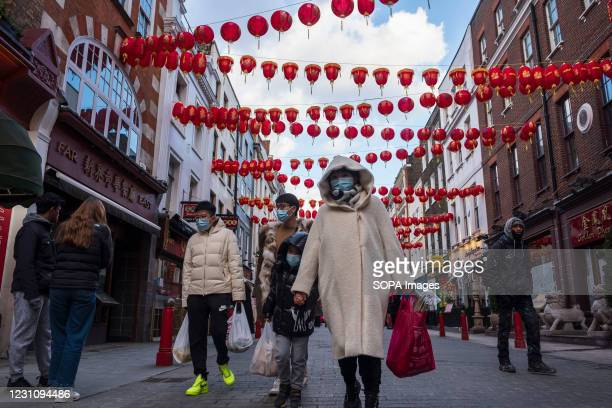 People wearing face masks as a preventive measure against the spread of covid-19 walk along the Street of China Town in London. Chinese New Year is...