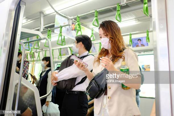 People wearing face masks as a preventive measure against the spread of covid-19 seen in a train at Shinagawa Station. Prime Minister Yoshihde Suga...