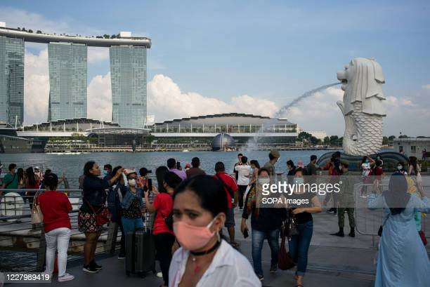 People wearing face masks as a preventive measure are seen at the Merlion park, one of the major tourist attraction in Singapore with the Marina Bay...
