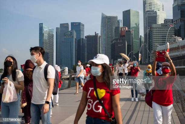 People wearing face masks as a preventive measure walk along the esplanade bridge during the Singapore National Day. Singapore celebrates its 55th...