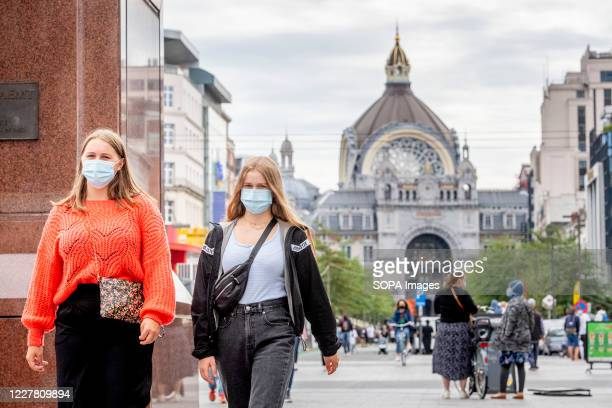 People wearing face masks as a preventive measure walk on the street during the coronavirus crisis. The wearing of a face mask will become compulsory...