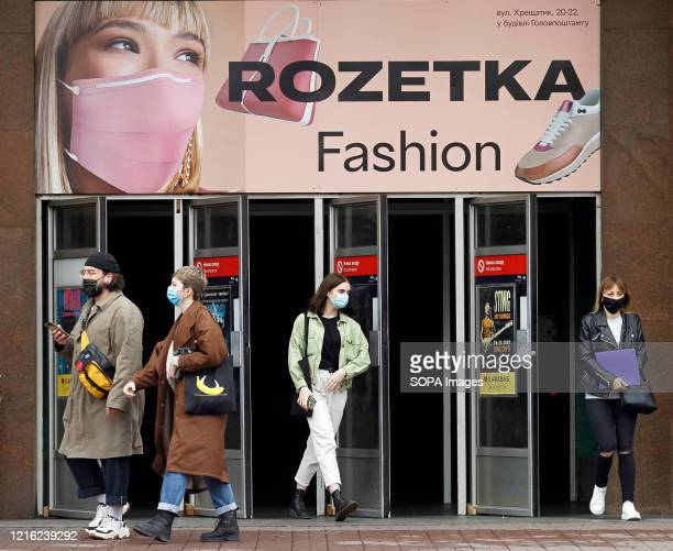 People wearing face masks as a preventive measure walk past Rozetka fashion store during the coronaviruus crisis Ukraine's government Plans to...