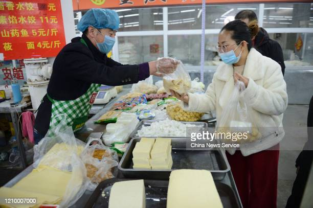 People wearing face masks buy food at a market amid novel coronavirus spread on March 2 2020 in Hohhot Inner Mongolia Autonomous Region of China