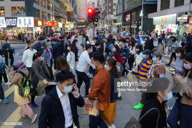 People wearing face masks corss a street at Wan Chai District on February 16, 2021 in Hong Kong, China.