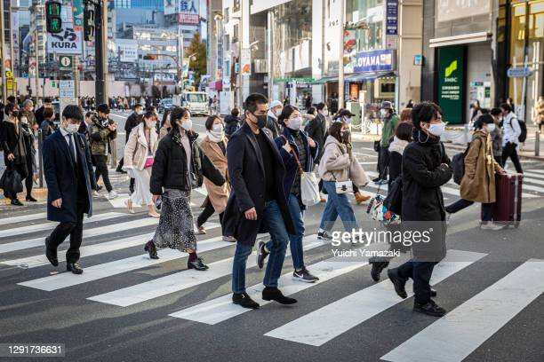 People wearing face masks cross a road on December 17, 2020 in Tokyo, Japan. Tokyo confirmed a record high of 822 new cases of Covid-19 coronavirus...