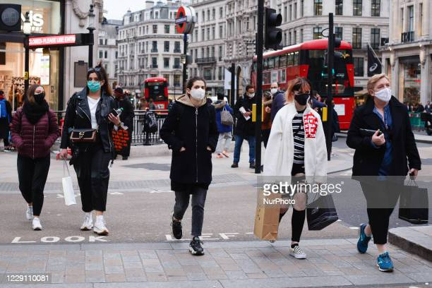 People wearing face masks cross Oxford Circus in London, England, on October 16, 2020. London is to be placed under 'Tier 2' coronavirus lockdown...
