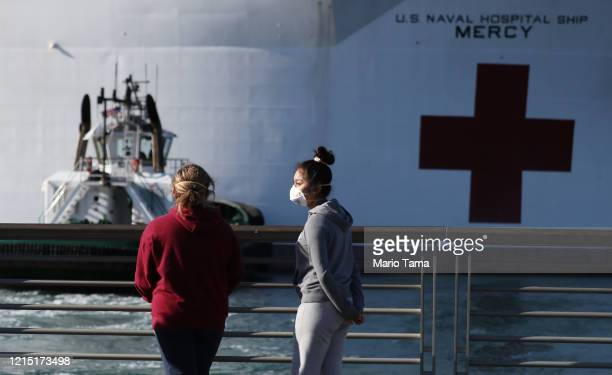 People wearing face masks gather near the USNS Mercy Navy hospital ship after it arrived in the Port of Los Angeles to assist with the coronavirus...