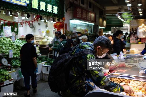 People wearing face masks in a wet market as residents in Mei Foo district protest against government plans to convert the Jao Tsung-I Academy a...