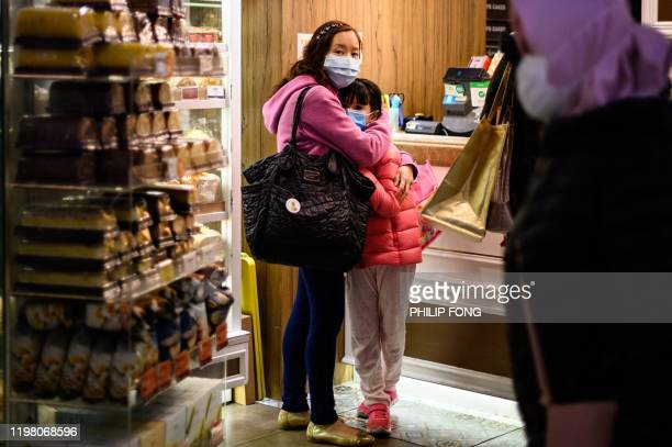 People wearing face masks inside a bakery react as residents in Mei Foo district protest against government plans to convert the Jao Tsung-I Academy...
