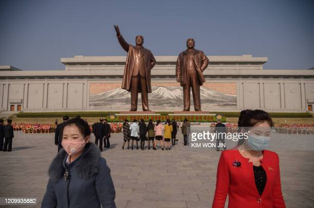 People wearing face masks leave after laying flowers before the statues of late North Korean leaders Kim Il Sung and Kim Jong Il on the occasion of...