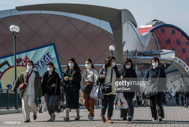 People wearing face masks leave Tokyo Disneyland on the day it announced it will close until March 15th because of concerns over the Covid19 virus on...