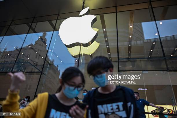 People wearing face masks look at a cellphone outside an Apple store during a May Day holiday in Shanghai on May 1 2020 With optimism and a heavy...