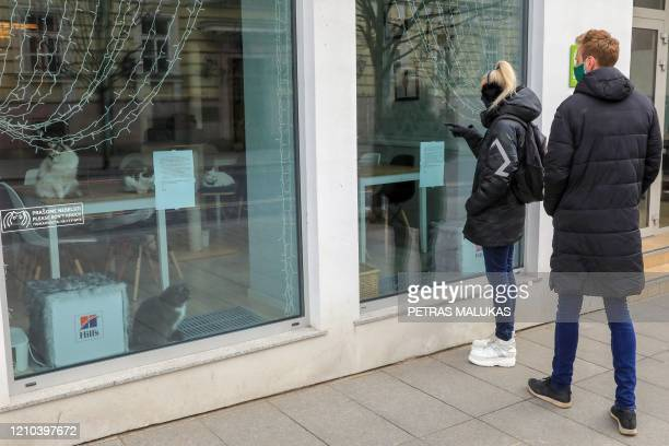 """People wearing face masks look at cats sitting behind the window of the """"Cat Cafe"""" which remains closed in Vilnius, Lithuania on April 19 amid the..."""