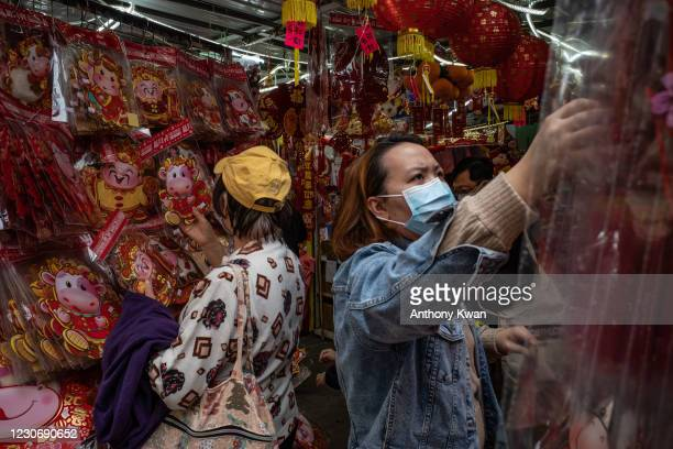 People wearing face masks look at Lunar New Year decorations at a market where COVID-19 cases have been confirmed in the Sham Shui Po district on...