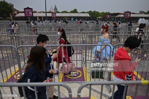 People wearing face masks maintaining social distancing as they enter the Disneyland amusement park in Shanghai on May 11 2020 Disneyland Shanghai...
