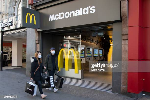 People wearing face masks pass McDonalds, which is now closed as a sit down fast food restaurant, but still open for take away orders on Oxford...