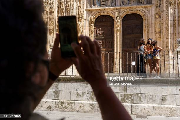 People wearing face masks pose for a picture in front of the cathedral in Aranda de Duero, near Burgos, on August 7 on the first day of a two week...